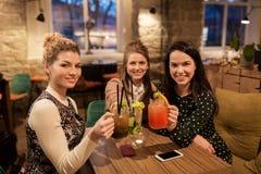 Amigos felices que tintinean bebidas en el restaurante Fotos de archivo libres de regalías