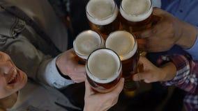 Amigos felices que tintinean los vidrios de cerveza en el pub, igualando el entretenimiento después de trabajo almacen de metraje de vídeo