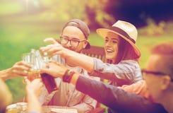 Amigos felices que tintinean los vidrios en el jardín del verano Imágenes de archivo libres de regalías