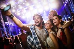 Amigos felices que toman el selfie en el festival de música imagen de archivo libre de regalías