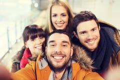 Amigos felices que toman el selfie en pista de patinaje Foto de archivo libre de regalías