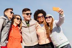 Amigos felices que toman el selfie por smartphone al aire libre Imágenes de archivo libres de regalías
