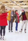 Amigos felices que toman la foto en pista de patinaje Imágenes de archivo libres de regalías