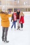 Amigos felices que toman la foto en pista de patinaje Foto de archivo