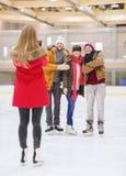 Amigos felices que toman la foto en pista de patinaje Foto de archivo libre de regalías