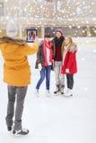 Amigos felices que toman la foto en pista de patinaje Fotos de archivo libres de regalías