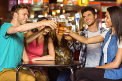 Amigos felices que tuestan con la bebida y la cerveza Fotografía de archivo