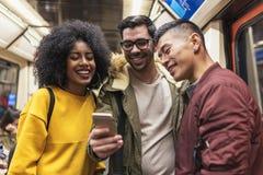 Amigos felices que usan el móvil en el carro del tren Foto de archivo