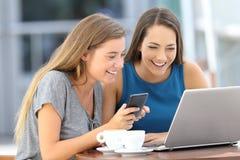 Amigos felices que usan un ordenador portátil y un teléfono en una barra Fotos de archivo libres de regalías