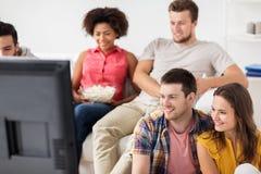 Amigos felices que ven la TV en casa Foto de archivo