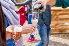 Amigos felices que vierten el vino espumoso del champán en los vidrios al aire libre Partido de la puesta del sol foto de archivo