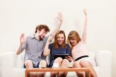 Amigos felizes bem sucedidos com tabuleta em casa Imagens de Stock Royalty Free