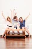 Amigos felizes bem sucedidos com tabuleta em casa Fotos de Stock Royalty Free