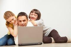 Amigos felizes com computador portátil Imagem de Stock Royalty Free