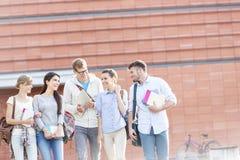 Amigos felizes com livros que falam ao andar no campus universitário fotos de stock royalty free