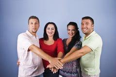 Amigos felizes com mãos junto Imagem de Stock