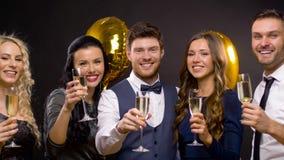 Amigos felizes com vidros do champanhe no partido filme