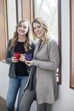 Amigos felizes das mulheres em casa com canecas imagem de stock royalty free