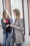 Amigos felizes das mulheres em casa com canecas fotos de stock royalty free