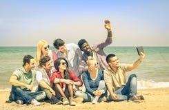 Amigos felizes multirraciais que tomam o selfie com a tabuleta na praia Foto de Stock