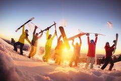Amigos felizes na estância de esqui que tem o por do sol do divertimento fotografia de stock