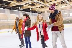 Amigos felizes na pista de patinagem Fotos de Stock