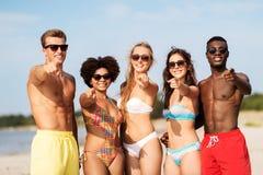 Amigos felizes na praia do verão que apontam a você foto de stock