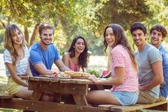 Amigos felizes no parque que tem o almoço Imagens de Stock Royalty Free