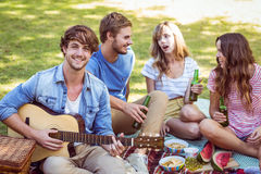 Amigos felizes no parque que tem o piquenique Imagem de Stock Royalty Free