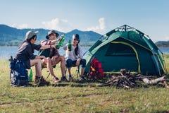 Amigos felizes no partido de acampamento que tem o divertimento junto e beber imagens de stock royalty free