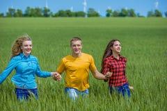 Amigos felizes novos que correm no campo de trigo verde Fotografia de Stock Royalty Free