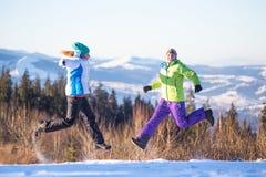Amigos felizes novos que têm o divertimento em montanhas do inverno foto de stock