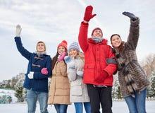 Amigos felizes que acenam as mãos na pista de gelo fora Fotografia de Stock Royalty Free