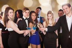 Amigos felizes que brindam bebidas no clube noturno imagens de stock