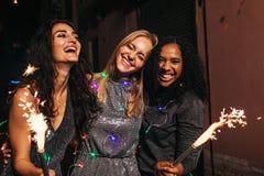 Amigos felizes que comemoram o ano novo com os chuveirinhos na noite imagens de stock royalty free