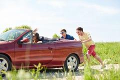 Amigos felizes que empurram o carro quebrado do cabriolet Fotografia de Stock