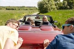 Amigos felizes que empurram o carro quebrado do cabriolet Fotografia de Stock Royalty Free