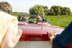 Amigos felizes que empurram o carro quebrado do cabriolet Foto de Stock Royalty Free