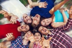 Amigos felizes que encontram-se junto no círculo Imagens de Stock