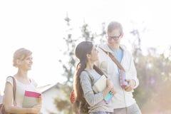 Amigos felizes que falam ao andar no campus universitário contra o céu fotografia de stock