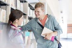 Amigos felizes que falam na biblioteca na faculdade imagens de stock