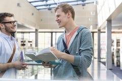 Amigos felizes que falam quando livros de leitura no corredor da universidade imagem de stock royalty free