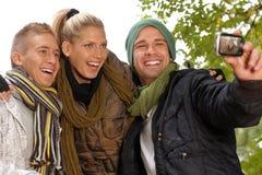 Amigos felizes que fotografam-se no parque imagens de stock