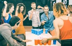 Amigos felizes que jogam o pong da cerveja na pousada da juventude - conceito do curso e da alegria com os mochileiros que descon foto de stock