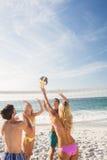 Amigos felizes que jogam o voleibol de praia fotografia de stock