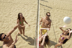 Amigos felizes que jogam o voleibol na praia Fotografia de Stock
