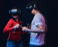 Amigos felizes que jogam os jogos de vídeo que vestem vidros da realidade virtual com controladores imagens de stock