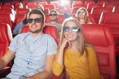 Amigos felizes que olham o filme no teatro 3d Fotografia de Stock Royalty Free