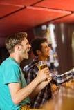 Amigos felizes que sentam e que bebem a cerveja Foto de Stock