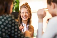 Amigos felizes que sentam-se e que falam no café Fotografia de Stock Royalty Free